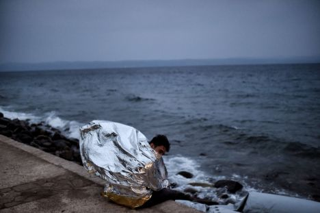 A young man sits wrapped in an emergency blanket after spending the night on the street with other refugees and migrants at the Greek island of Lesbos after crossing the Aegean sea from Turkey on October 8, 2015. Europe is grappling with its biggest migration challenge since World War II, with the main surge coming from civil war-torn Syria. AFP PHOTO / ARIS MESSINIS